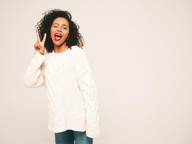 Красивая темнокожая женщина с прической афро кудри и красными губами. улыбающаяся модель в модной джинсовой одежде и зимнем свитере.