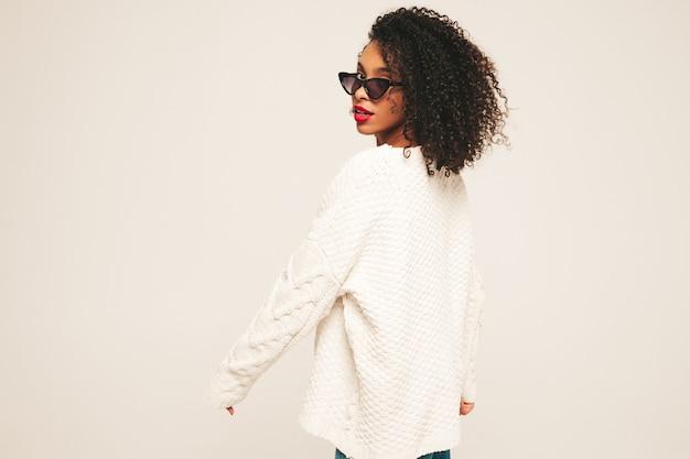 아프로 컬 헤어스타일과 붉은 입술을 가진 아름다운 흑인 여성. 최신 유행의 청바지 옷과 겨울 스웨터를 입은 웃는 모델.