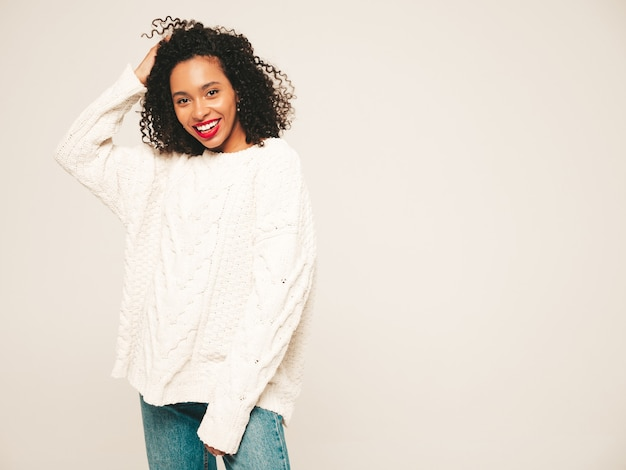 Beautiful black woman with afro curls hairstyle and red lips.smiling model in  trendy jeans clothes and winter sweater.