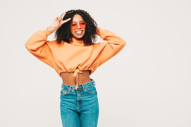 アフロカールの髪型を持つ美しい黒人女性。オレンジ色のパーカーと流行のジーンズの服で笑顔モデル