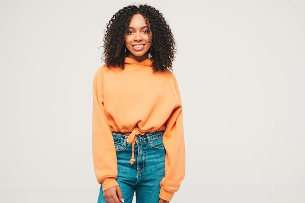 아프리카 컬 헤어스타일을 가진 아름 다운 흑인 여성입니다. 주황색 후드티와 트렌디한 청바지 옷을 입은 웃는 모델