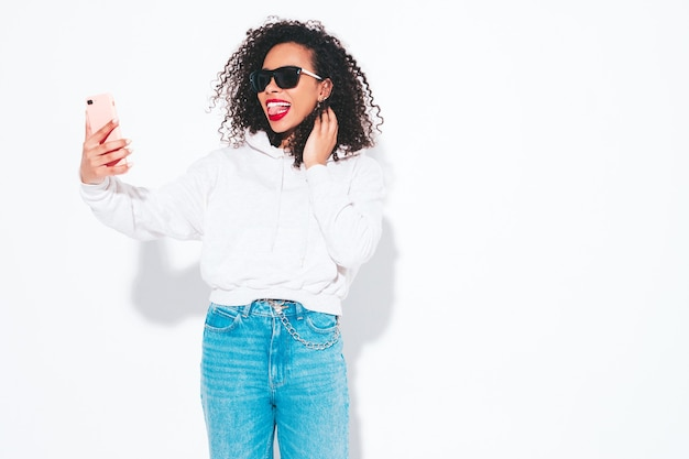 アフロカールの髪型を持つ美しい黒人女性。夏服の笑顔モデル