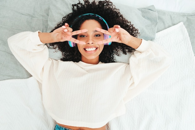 아프리카 컬 헤어스타일을 가진 아름 다운 흑인 여성입니다. 스웨터와 청바지에 웃는 모델. 아침에 무선 헤드폰으로 평온한 여성 듣기 음악