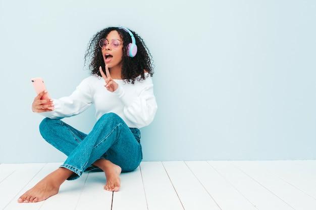 아프리카 컬 헤어스타일을 가진 아름 다운 흑인 여성입니다. 스웨터와 청바지에 웃는 모델. 무선 헤드폰에서 평온한 여성 듣기 음악