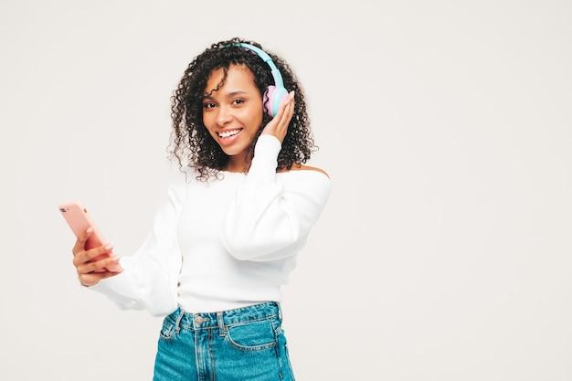 아프리카 컬 헤어스타일을 가진 아름 다운 흑인 여성입니다. 스웨터와 청바지에 웃는 모델