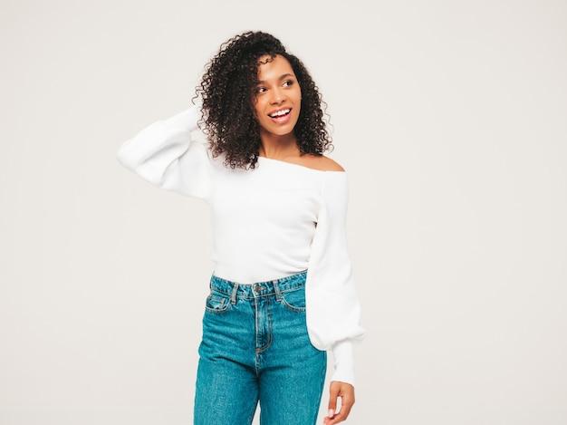 아프리카 컬 헤어스타일을 가진 아름 다운 흑인 여성입니다. 스웨터와 트렌디한 청바지 옷을 입은 웃는 모델.