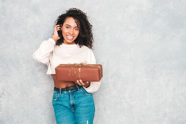 アフロカールの髪型を持つ美しい黒人女性。白い流行のジーンズの服とサングラスの笑顔モデル。灰色の壁の近くでポーズをとる屈託のない女性。ギフトボックスを持っています。
