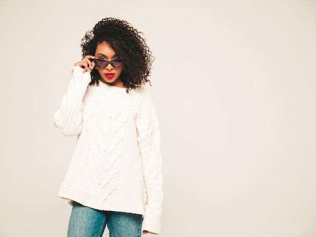 Красивая темнокожая женщина с прической афро кудри. улыбающаяся модель в белом зимнем свитере и джинсовой одежде и солнцезащитных очках.