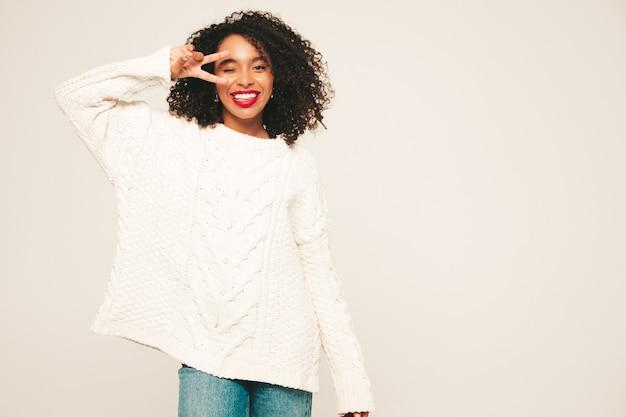 Красивая темнокожая женщина с прической афро кудри. улыбающаяся модель в белом зимнем свитере и джинсовой одежде.