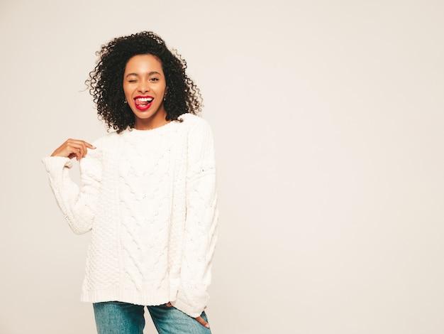 アフロカールの髪型を持つ美しい黒人女性。白い冬のセーターとジーンズの服の笑顔モデル。
