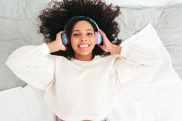 Bella donna di colore con l'acconciatura di riccioli afro. modello sorridente in maglione e jeans. spensierata musica d'ascolto femminile in cuffie wireless al mattino