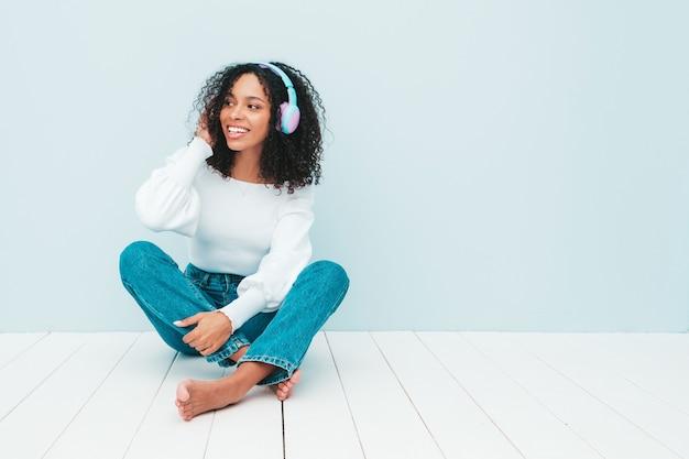 Bella donna di colore con l'acconciatura di riccioli afro. modello sorridente in maglione e jeans