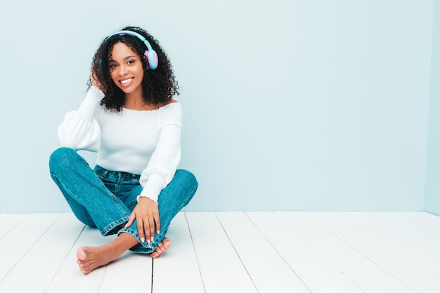 Beautiful black woman with afro curls hairstyle. smiling model in sweater and jeans