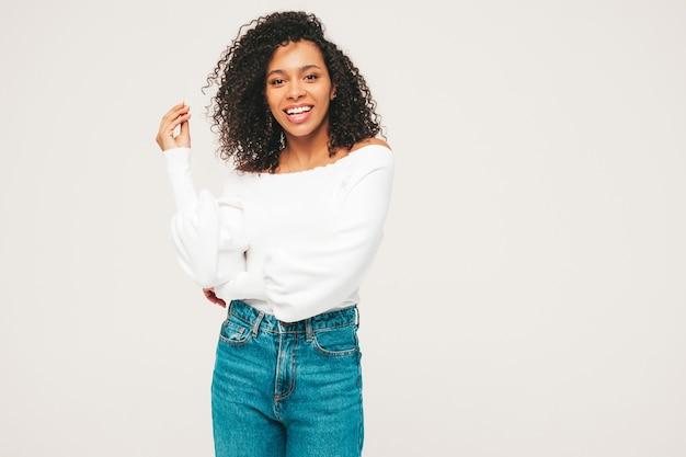 Bella donna di colore con l'acconciatura di riccioli afro. modello sorridente in maglione e vestiti di jeans alla moda