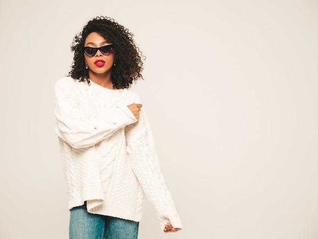 Bella donna di colore con l'acconciatura di riccioli afro. modello sorridente in maglione invernale bianco e vestiti di jeans e occhiali da sole.