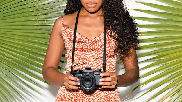 Beautiful black woman with an analog camera