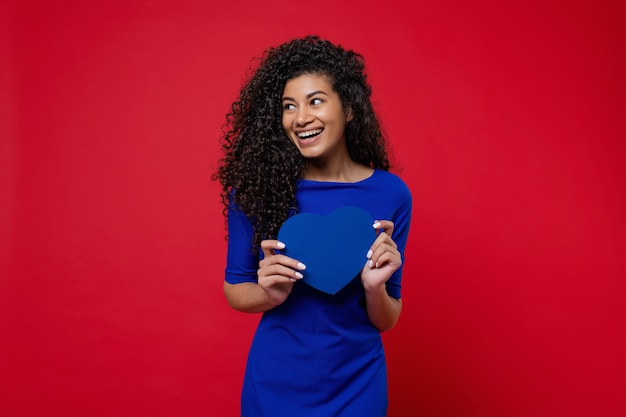 Beautiful black woman with blue heart shaped valentine card wearing dress on red wall