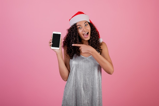 Beautiful black woman with copyspace screen on phone wearing christmas hat isolated over pink
