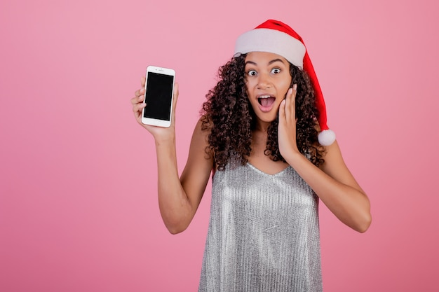 Beautiful black woman with copyspace screen on phone wearing santa hat isolated over pink