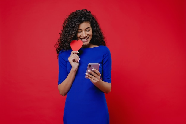 Beautiful black woman with heart shaped valentine card looking at phone on red wall
