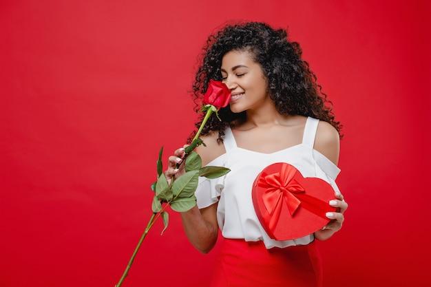 赤で分離されたローズとハート形のギフトボックスと美しい黒人女性