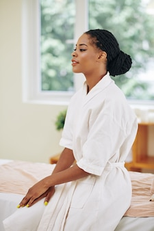 Beautiful black young woman in bath robe sitting on bed in spa salon after relaxing bath and waiting for massage therapist