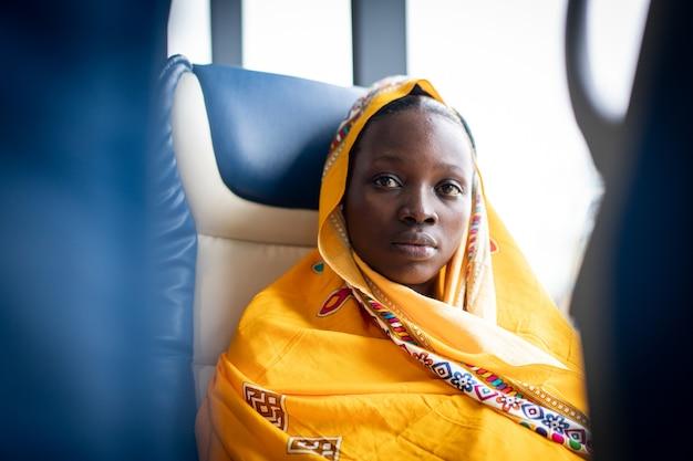 창 근처에서 혼자 여행하는 아름다운 흑인 젊은 여성
