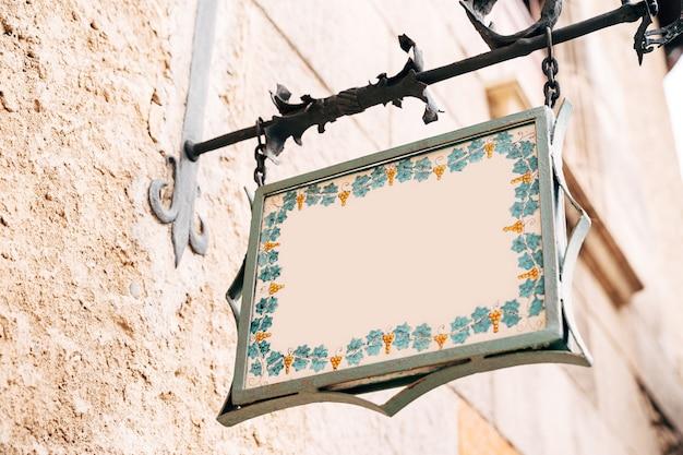 Красивая пустая доска причудливой формы висит в кованой рамке на фасаде дома.