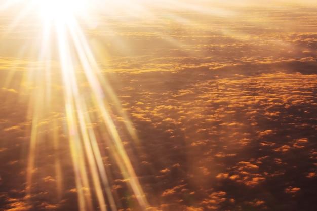 雲の上の美しい燃える日の出の風景。航空機からの眺め。日没と日の出の概念の背景。