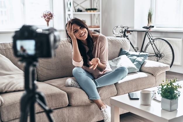 美しいブロガー。ソーシャルメディアビデオを作成し、屋内に座って笑っている女性のvlogger