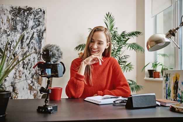 ソーシャルメディアのビデオを録画し、見ながら笑っている美しいブロガー女性若いvlogger