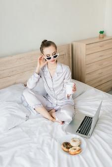 Красивая блондинка женщина учится и работает в постели со своим ноутбуком