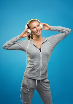 Beautiful blond fit caucasian lady in grey sport with headphones listening music. isolated on blue wall