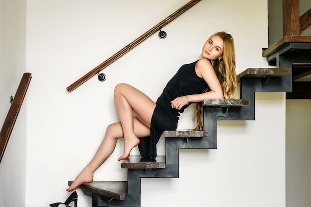 Beautiful blond girl in black dress sits on the stairs