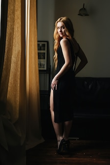 Beautiful blond girl in a black dress stands in the interior and looks out the window,