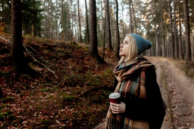 Beautiful blond girl in blue hat with cup of coffee in a forest
