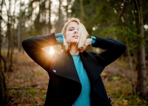 Beautiful blond girl in blue sweater in a forest