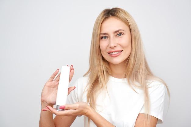 Красивая блондинка демонстрирует косметический продукт, держа бутылку по уходу за кожей на белом фоне