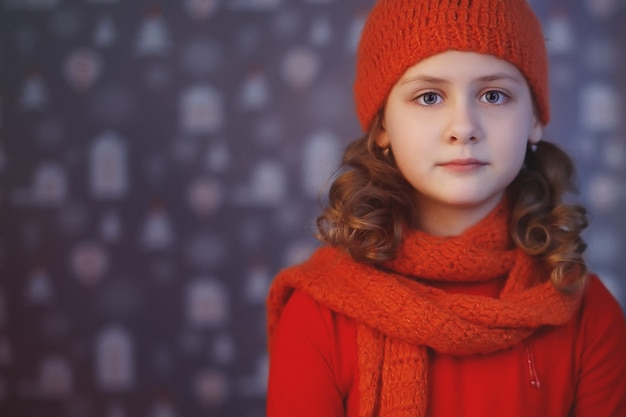 Beautiful blond girl dressed in warm winter hat and scarf, cold and warm hands