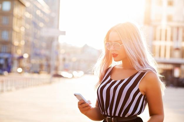 携帯電話を持ってメッセージを入力する美しいブロンドの女の子