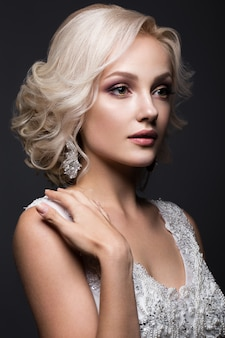 Beautiful blond girl in image of the bride with wedding accessories on her head. beauty face.