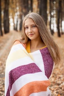 줄무늬 담요에 싸여가 공원에서 아름 다운 금발 소녀. 주황색과 노란색 색상, 쌀쌀한 날씨, 아늑한 분위기.