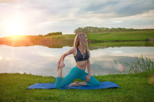A beautiful blond girl is practicing yoga on the lake at sunset. close-up