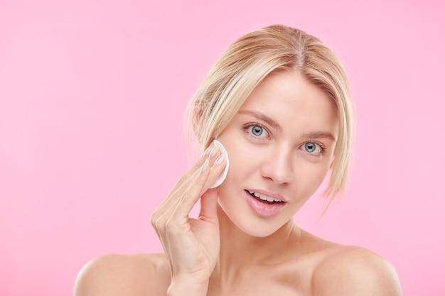 Красивая белокурая девушка с помощью ватного диска очищает лицо и снимает макияж над розовой стеной