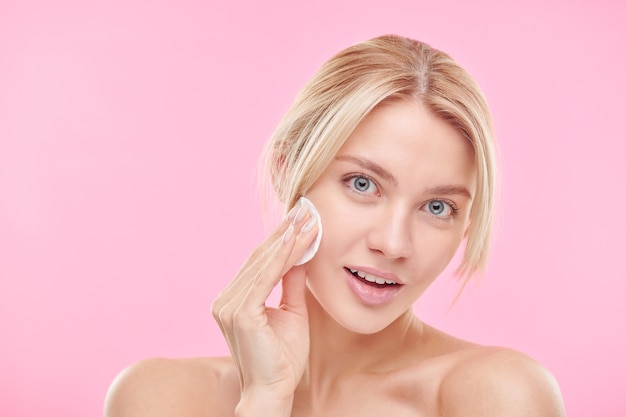 Beautiful blond girl using cotton pad while cleansing face and removing makeup over pink wall