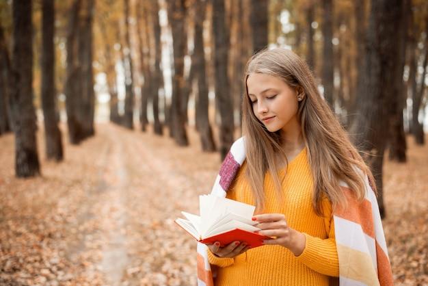 가을 공원에서 손에 책을 들고 있는 아름다운 금발 소녀
