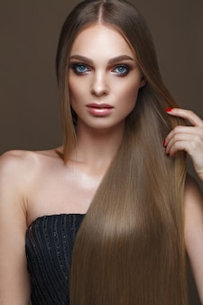 Beautiful blond girl with a perfectly smooth hair, classic make-up. beauty face