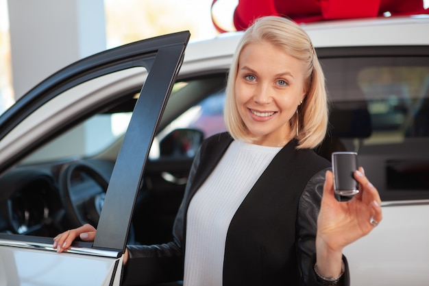 Beautiful blond haired woman smiling, holding car key at the dealership