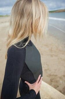Красивая блондинка в мокром костюме на пляже