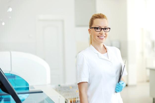 彼女の腕にタブレットを持って実験室に立っている白衣とゴム手袋の美しい金髪の実験室助手。